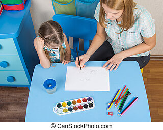Mentor and five year old girl at the table draw a picture in kindergarten