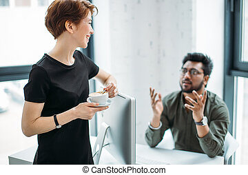 mentor boss smiling looking at young male coworker and drink coffee, teaching helping colleague