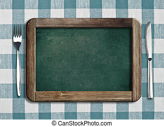 Menu blackboard lying on tablecloth with knife and fork