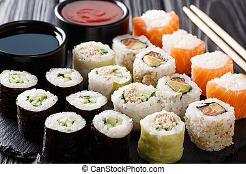 Menu set of Japanese rolls with salmon, tuna, avocado, cucumber served with sauces close-up on a stone. horizontal