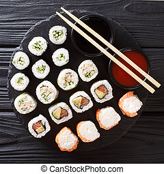 Menu set of Japanese rolls with salmon, tuna, avocado, cucumber served with sauces close-up on a stone. top view