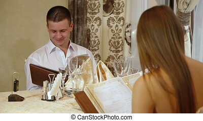 young couple dinner in a restaurant, choosing dishes from menu DOF focusing on women
