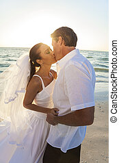 menyasszony inas, csókolózás, összekapcsol naplemente, tengerpart esküvő