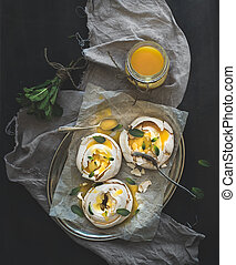 Merengues with lemon curd and fresh mint on silver tray, beige kitchen towel and grunge dark background