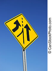 merge traffic sign against blue sky background