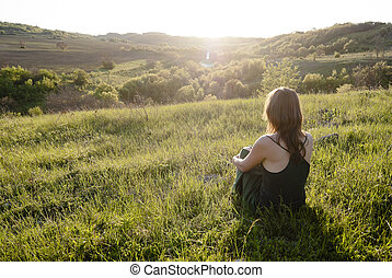Merging with Nature - Beautiful young woman sitting on the...