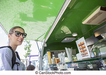 Young atractive woman ordering meal at green food truck