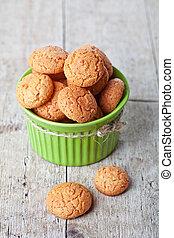 meringue almond cookies in bowl on wooden background