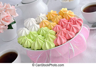 Meringue cookies of different colors on a plate with a cup of coffee