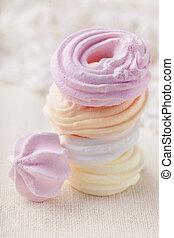 Pastel colored meringue on blue background