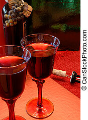 Glasses of merlot wine, the bottle with grapes around it and the dislodged cork sitting nearby.