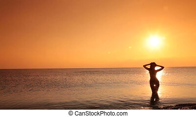 mermaid at sunset - silhouette of young woman in a bikini...