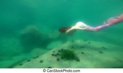 Underwater Mermaid is diving at clear sea