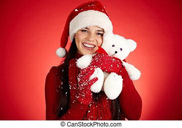 Merriment - Joyful girl in Santa cap with white teddy bear...