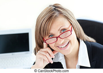 Merry businesswoman looking at the camera sitting in her office
