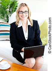 Merry businesswoman with glasses using her laptop on a sofa