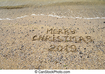 Merry Christmas 2019 written on tropical beach sand, copy space. Holiday concept, top view