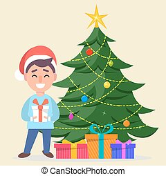 Boy in Santa Claus hat standing near decorated Christmas tree with gift boxes under it