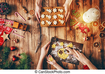 Merry Christmas and Happy Holidays! A mother, father and daughter prepare Xmas cookies. Baubles, presents, candy and cookies with christmas ornaments. Top view. Christmas family traditions.