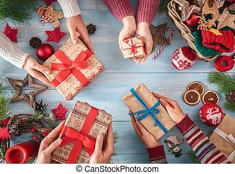 Merry Christmas and Happy Holidays! Grandmother, mother, father and their daughter preparing gifts. Baubles, presents, candy with ornaments. Top view. Xmas family traditions.