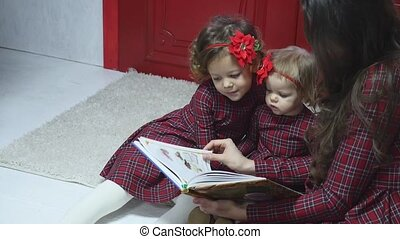 Merry Christmas and Happy Holidays Pretty young mom reading...
