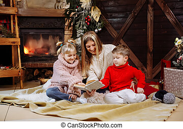 Merry Christmas and Happy New Year. Beautiful family in Xmas interior. Pretty young mother reading a book to her daughter and son near Christmas tree.