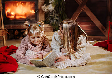 Merry Christmas and Happy New Year. Beautiful family in Xmas interior. Pretty young mother reading a book to her daughter near Christmas tree.