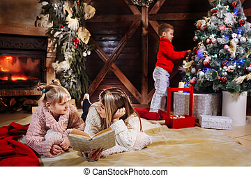 Merry Christmas and Happy New Year. Beautiful family in Xmas interior. Pretty young mother reading a book to her daughter. Son decorate Christmas tree.