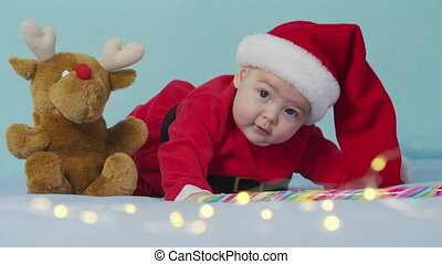Merry Christmas and happy new year, childhood, holidays concept close-up. 3 month old newborn baby in Santa Claus hat on his tummy crawls