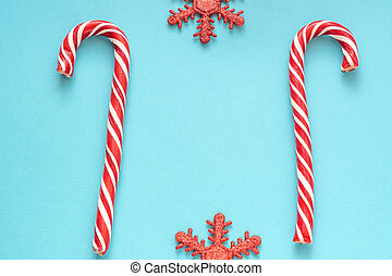 Merry Christmas and Happy New Year greeting card. Two candy canes and sparkling snowflakes on blue background with copy space for your text.