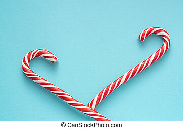 Merry Christmas and Happy New Year greeting card. Two candy canes on blue background with copy space for your text.