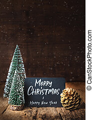 Merry Christmas and happy new year on blackboard with xmas tree and gold pine cone and snow falling on grunge wood table and dark brown wooden wall. winter holiday greeting card.