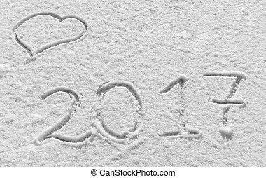 Merry Christmas and Happy New Year. Snowy background with hearts and the inscription 2017