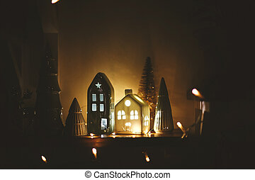 Merry Christmas and New Year. Christmas little houses with lights and trees in night. Miniature houses among pine tree in christmas evening. Stylish festive decorations, winter wonderland