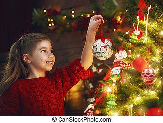 girl is decorating the Christmas tree - Merry Christmas!...