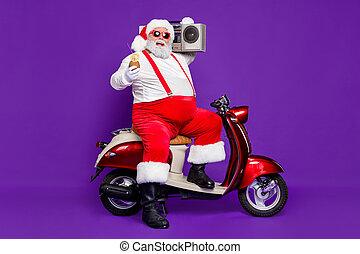 Merry christmas. Full body photo of santa man sitting on moped alcohol drink and vintage tape recorder on shoulder wear specs and costume isolated purple background