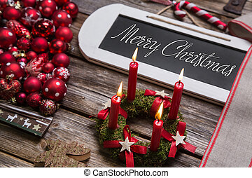 Merry christmas greeting card with four red candles and text.