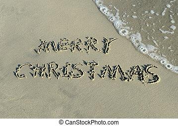 Merry Christmas handwritten in sand on a beautiful beach