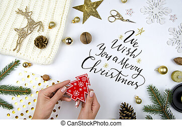 Merry Christmas lettering. Woman holding a red christmas tree. Fir branches and christmas decorations flat lay. Top view flatly composition