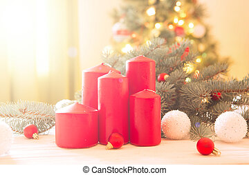 Merry Christmas! Red advent flower arrangement with burning candles on Cristmas Tree background
