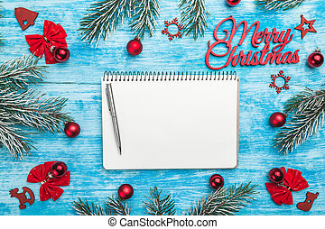 Merry Christmas sign, handmade evergreen tree toys, fir branches, with red ribbon in corners and notepad with pen for text view from top, above, on blue wooden background, Xmas greeting card