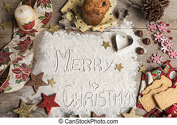 Merry Christmas, text made with flour, surrounded by Christmas decorations.