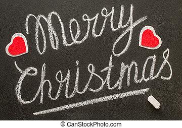 Merry Christmas text written on chalkboard.