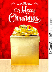 Merry Christmas with Golden Present box on wood table at red bokeh light background, Holiday concept