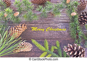 Merry Christmas with pine cones and needles on wooden background