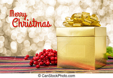 Merry Christmas word with Gold present box and ribbon on table with sparkling gold bokeh light background, Holiday concept