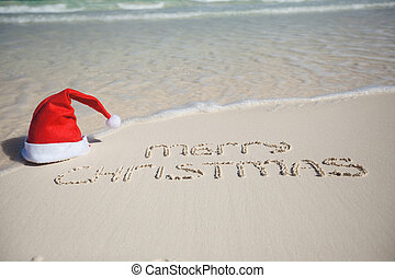 merry christmas written on tropical beach white sand with xmas hat - Merry Christmas Beach Images