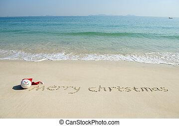 Merry Christmas written on tropical beach white sand with xmas snowman