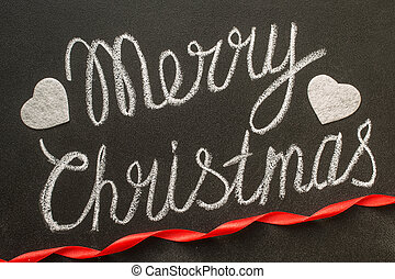 Merry Christmas written with chalk on a chalkboard.
