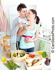 Merry couple drinking wine in the kitchen